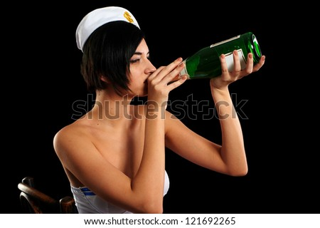 Young beautiful woman in sailor costume with wine bottle. Isolated on black - stock photo