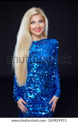 Young beautiful woman in shiny dress on black background. Disco . - stock photo