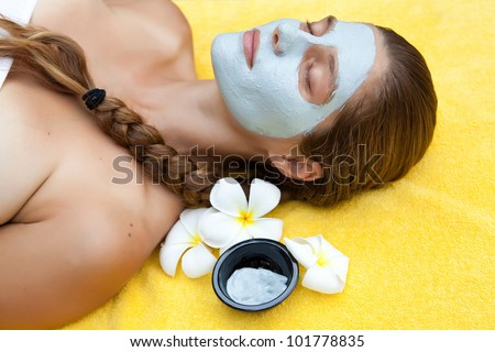 Young beautiful woman in spa making face treatment - stock photo