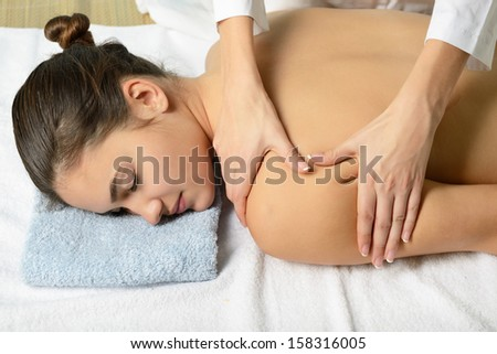 Young beautiful woman in spa salon gets massage - stock photo