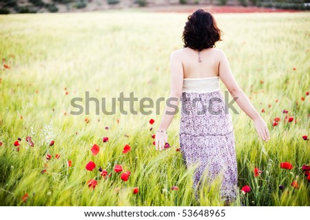 Young beautiful woman in spring field - stock photo