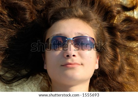 Young beautiful woman in sunglasses lying with spread hair in the sun - stock photo