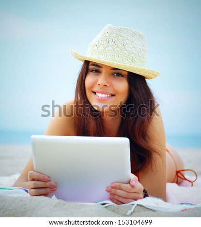 Young beautiful woman in swimming suit using her tablet on the beach - stock photo