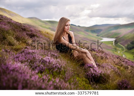 young beautiful woman  in the heather meadows in Scotland - stock photo