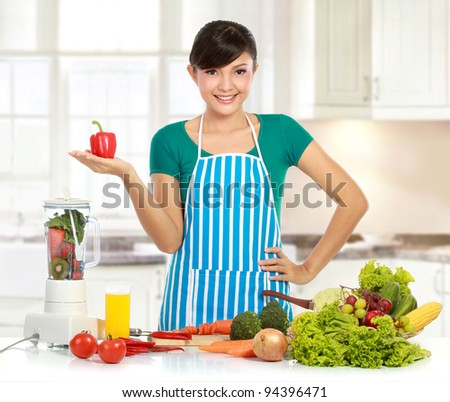 young beautiful woman in the kitchen with many ingredient ready to cook some food - stock photo
