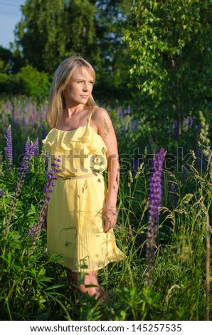 Young beautiful woman in the lupine field