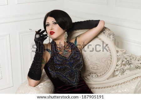 Young beautiful woman in thirties costume with tattoos and cigarette holder - stock photo