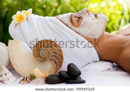 Young beautiful woman in tropical spa making face mask treatment - stock photo