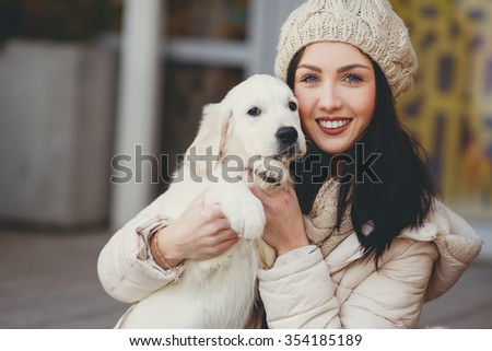 young beautiful woman in warm clothes with white labrador retrievers. dogs and woman. outdoor portrait. Pets and girl. Beautiful woman playing with her dog. Outdoor portrait. series