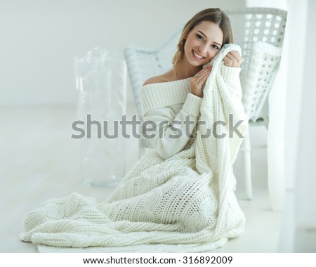 Young beautiful woman in warm knitted handmade clothes at home. Model fashion shooting. Autumn, winter season.  - stock photo