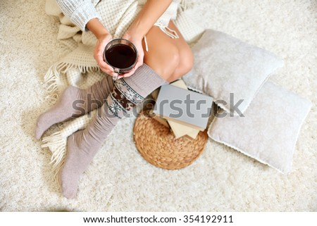 Young beautiful woman in warm knitted handmade clothes at home. Model fashion shooting. Autumn, winter season. Gaiters. Golfs. Leggings. - stock photo