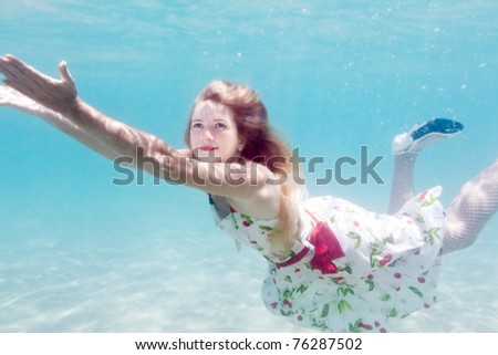 Young beautiful woman in white dress underwater - stock photo