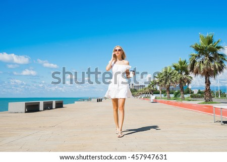 Young  beautiful woman in white dress walking on the beach boulevard with coffee cup and talking on mobile.