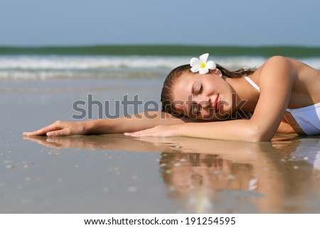 Young beautiful woman in white swimwear lying on the beach