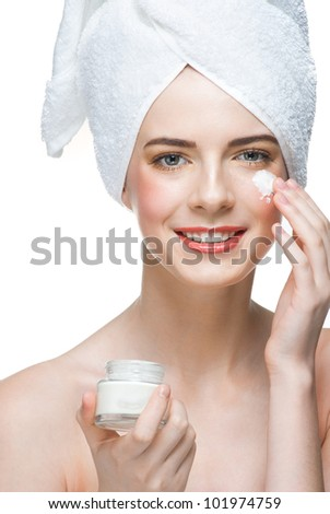 Young beautiful woman in white towel applying moisturizing cream on her face, isolated on white background