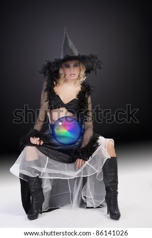 young beautiful woman in witch black dress with hat and a long gown holding a magic crystal