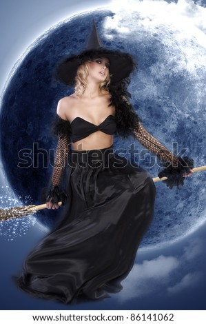 young beautiful woman in witch black dress with hat and a long gown pulling face and sitting on broom - stock photo