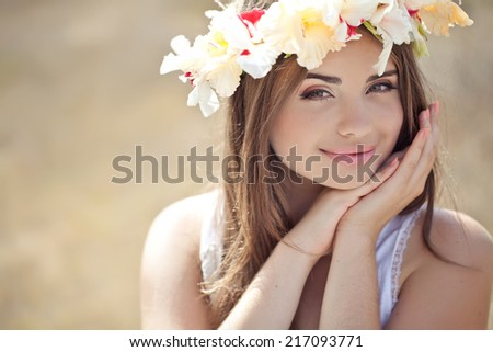 young beautiful woman in wreath of flowers  outdoors in nature - stock photo