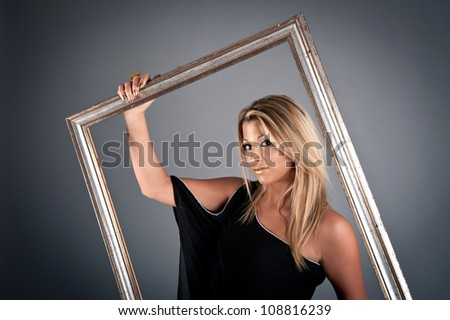 Young beautiful woman inside an antique picture frame on dark background.