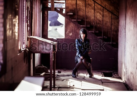 Young beautiful woman inside rusty building.