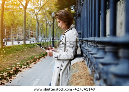 Young beautiful woman is booking on-line via portable touch pad, while is standing on the street in autumn day. Female dressed in spring clothes is reading information in internet via digital tablet - stock photo
