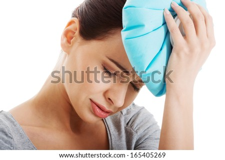 Young beautiful woman is haveng a headache and holding ice bag. Isolated on white.