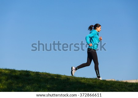 Young beautiful woman is jogging in a sunny day