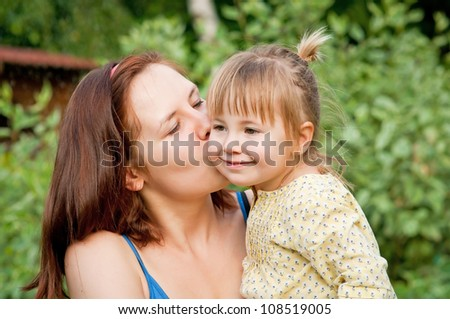 Young beautiful woman is kissing a little baby girl - stock photo