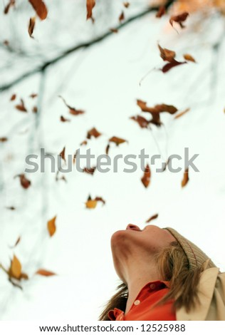 Young beautiful woman is looking up as leaves are slowly falling down? Concept: beauty, wonder, innocence, enjoyment - stock photo
