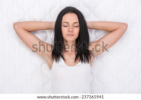 Young, beautiful woman is lying on the bed. Quality mattress. - stock photo