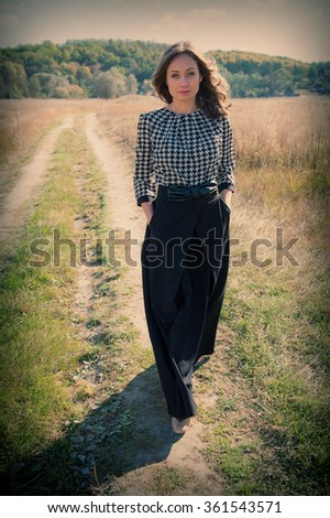 young beautiful woman is on the road in the field on the background of the rural landscape