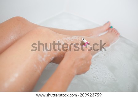 Young beautiful woman is shaving legs in the bathtub - stock photo