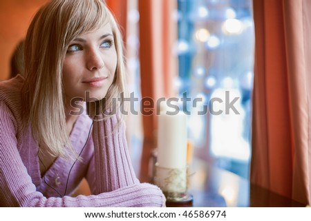 Young beautiful woman is sitting in cafe alone - stock photo
