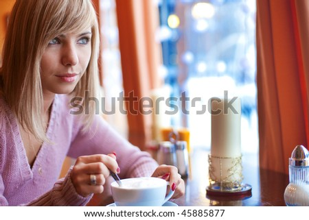 Young beautiful woman is sitting in cafe with a white cup and reading the newspaper