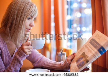 Young beautiful woman is sitting in cafe with a white cup and reading the newspaper - stock photo