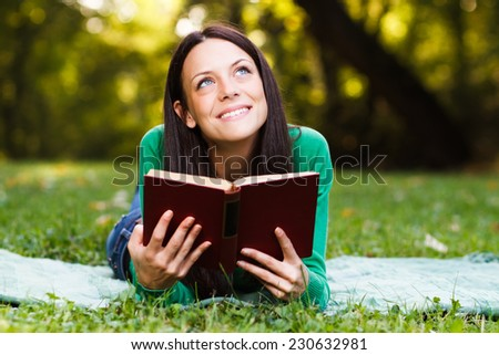 Young beautiful woman is thinking about something while reading a book,Leisure time