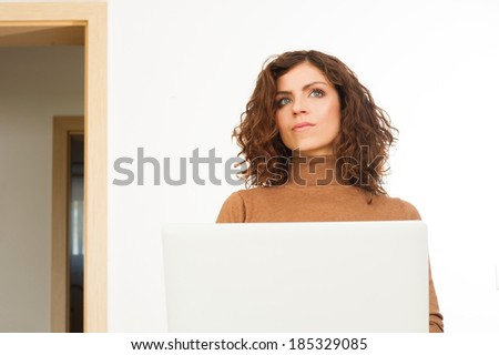 Young beautiful woman is thinking while she using a laptop computer at home - stock photo