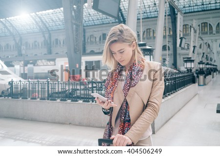 young beautiful woman is using a smartphone while waiting for a train as arrival. attractive young blonde woman using smart-phone while standing on the railway station platform - stock photo