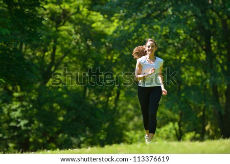 Young beautiful  woman jogging on morning at  park. Woman in sport outdoors health concept - stock photo
