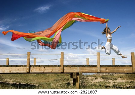 Young beautiful woman jumping with a scarf - stock photo