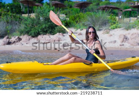 Young beautiful woman kayaking alone in the clear blue sea