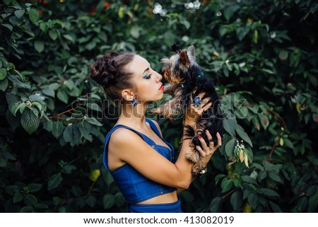 Young beautiful woman kisses Yorkshire Terrier near green bush