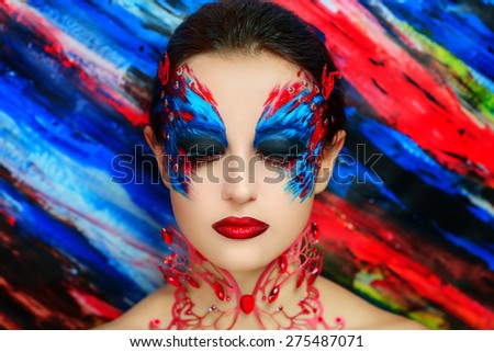Young beautiful woman, lady, model, woman, character, butterfly,bird, firebird , ice queen. Creative, perfect, fantasy makeup. Bright, saturated colors, red, blue, mask, eyes. Fairytale, stylish look. - stock photo