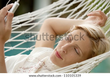 Young beautiful woman laying down on a hammock while on vacations in a tropical destination hotel, outdoors by the swimming pool and listening to music with her earphones. - stock photo