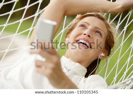Young beautiful woman laying down on a hammock while on vacations in a tropical destination hotel's garden and listening to music with her earphones and smiling. - stock photo