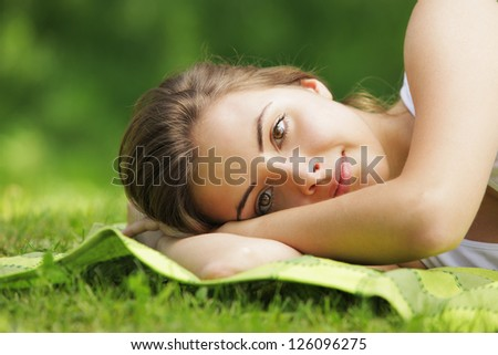 Young beautiful woman laying on the grass, close up