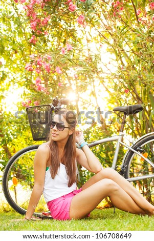 young beautiful woman laying on the grass in summer - stock photo