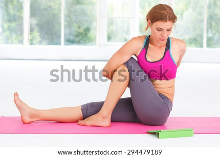 Young beautiful woman learning yoga with tablet. - stock photo