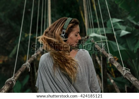 Young beautiful woman listen to the music on suspension bridge in the tropic forest