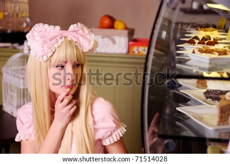 Young beautiful woman looking at cakes. - stock photo